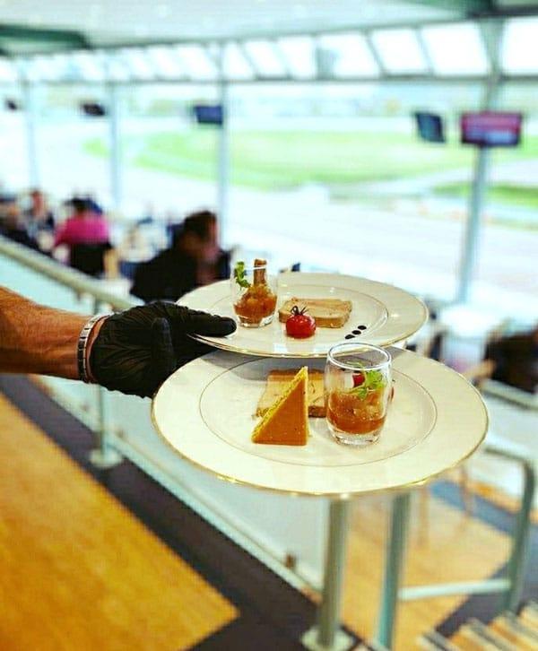 Photo de 2 assiettes dans la main d'un serveur Ménard Traiteur Caen à l'hippodrome de Cabourg